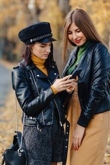 Twee comfortabele jonge meisjes lopen bij de weg van het de herfstpark maken foto's