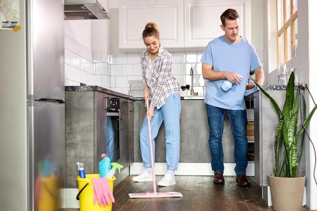 Twee conciërges die de keuken schoonmaken en de vloer thuis dweilen, blanke man en vrouw in casual weae genieten van het huishouden, schoonmaken van plat appartement