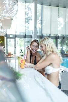 Twee coole trendy mooie grappige gelukkig sexy gebruinde vrouwen met een cocktail, naast het zwembad in het resort