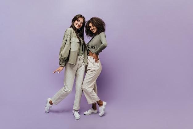 Twee coole vrouwen glimlachen met donkerbruin kapsel in olijfkleurige overhemden, beige wijde broeken en witte trendy sneakers die in de camera kijken