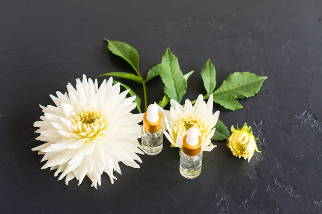 Twee cosmetische flessen van transparant glas met healcronic zuur op een zwarte achtergrond met witte bloemen. het concept van schoonheid en huidverzorging.