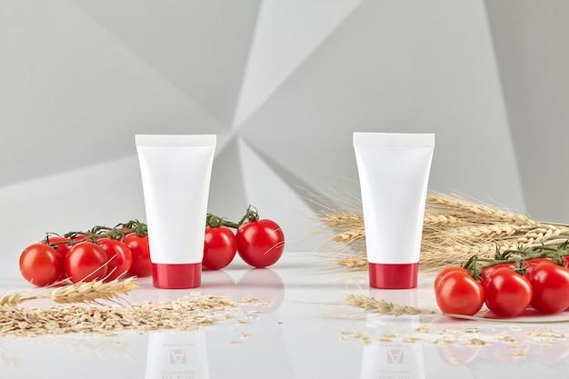 Twee cosmetische tubes met rode doppen