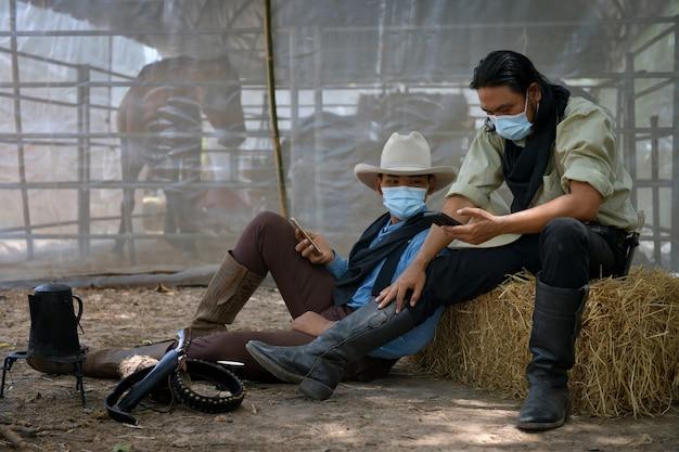 Twee cowboymannen dragen een masker om de verspreiding van de ziekte te voorkomen. covid 19, quarantaineconcept