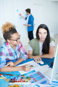 Twee creatieve jonge vrouwen die werken in office