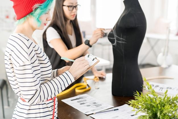 Twee creatieve modeontwerpers werken in atelier workshop