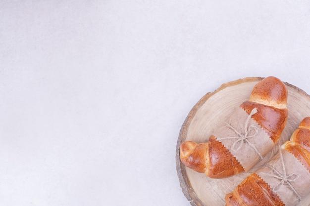 Twee croissantbroodjes in papieromslag op een houten bord.