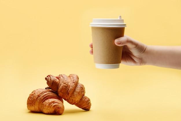 Twee croissants en een hand met een papieren beker voor koffie en thee