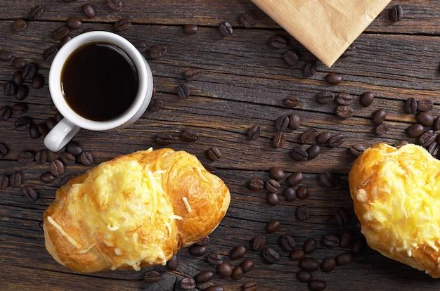 Twee croissants met kaas en kopje zwarte koffie op oude houten ondergrond, bovenaanzicht