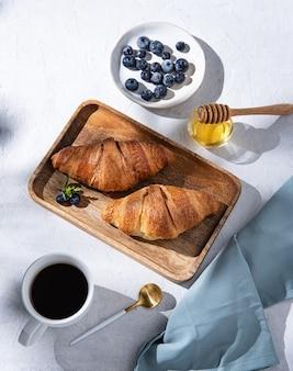 Twee croissants op een snijplank met kopje koffie, honing en bosbessen