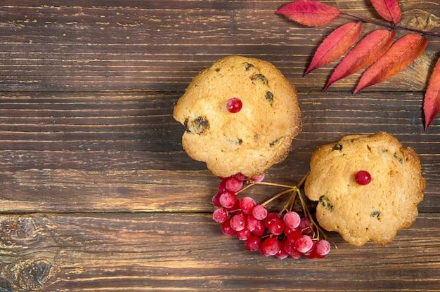 Twee cupcakes met rode bessen en rode herfstbladeren op een houten tafel