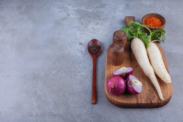 Twee daikon radijs en rode uien op een houten bord.
