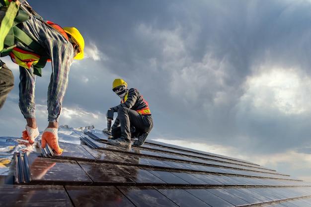 Twee dakdekkers in veiligheidskleding werken als een team om het dak van het huis dat keramische pannendak op de bouwplaats te plaatsen