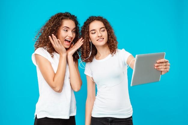 Twee dames tweeling maken selfie op tablet over blauw.