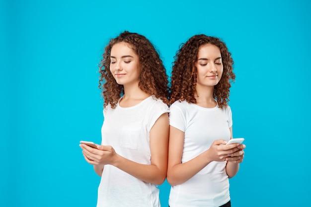 Twee dames tweelingen glimlachen, kijken naar telefoons over blauw.