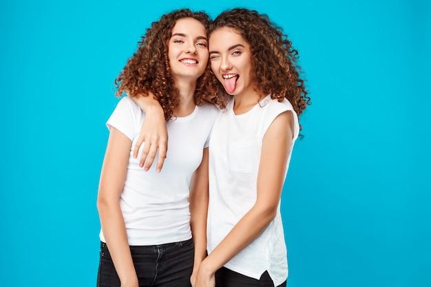 Twee dames tweelingen glimlachen, tong tonen over blauw.