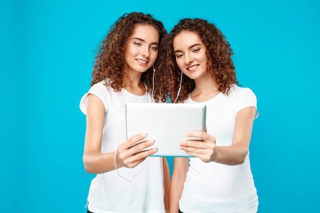 Twee dames tweelingen kijken naar tablet, glimlachend over blauw.
