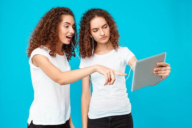 Twee dames tweelingen kijken naar tablet, verrast over blauw.