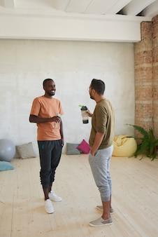 Twee dansers die water drinken en nieuwe oefeningen bespreken na sporttraining in dansstudio