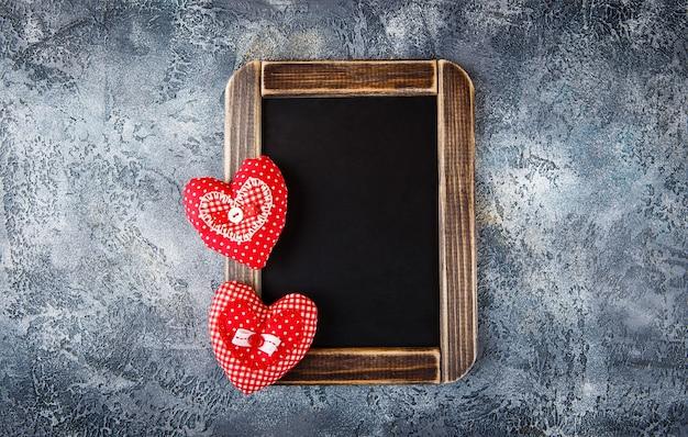 Twee decoratieve handgemaakte harten van textiel en een schoolbord voor valentijnsdag op blauwe betonnen tafel