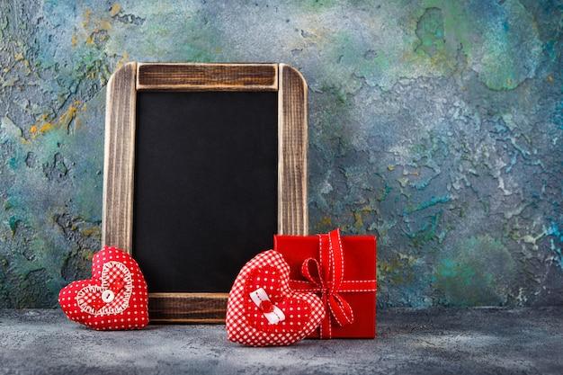 Twee decoratieve handgemaakte harten van textiel, rode geschenkdoos en schoolbord voor valentijnsdag op blauwe betonnen tafel