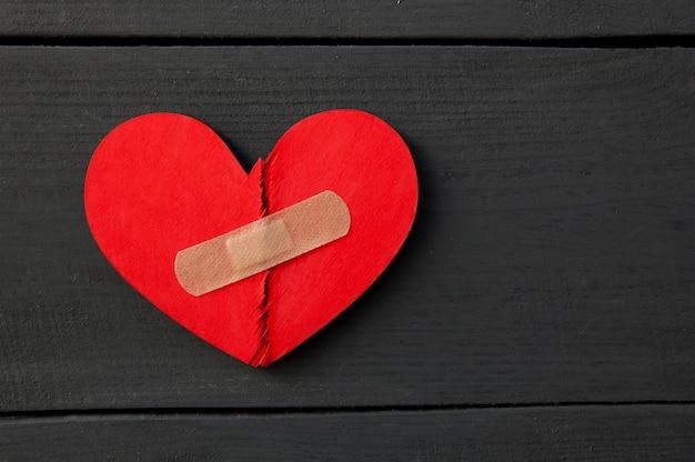 Twee delen van rood gebroken houten hart geplakt door een patch