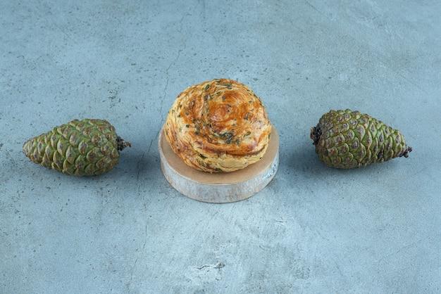Twee dennenappels en een schilferige cake op marmer.