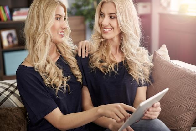 Twee dezelfde zussen met moderne tablet