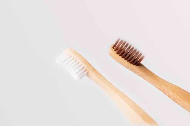 Twee diagonale houten tandenborstels, één met witte haren en de andere bruin op een lichte achtergrond