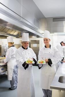 Twee die de zalmschotels glimlachen van de chef-kok