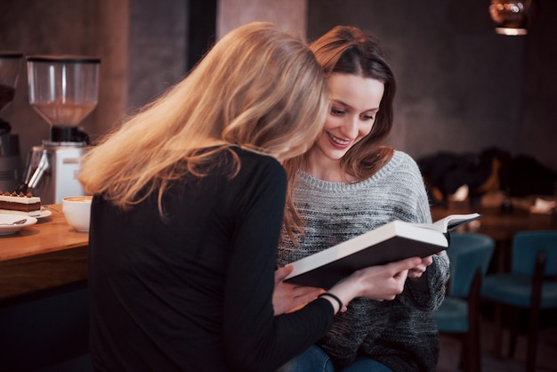 Twee die meisje `s in lezingsboek tijdens de onderbreking in koffie wordt geabsorbeerd. leuke mooie jonge vrouwen lezen boek en drinken koffie