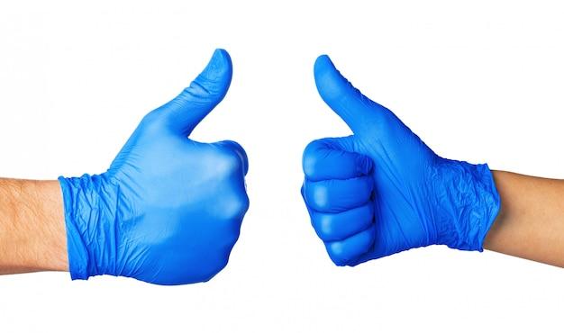 Twee dienen blauwe handschoenen in die op wit met omhoog duim worden geïsoleerd, sluiten omhoog