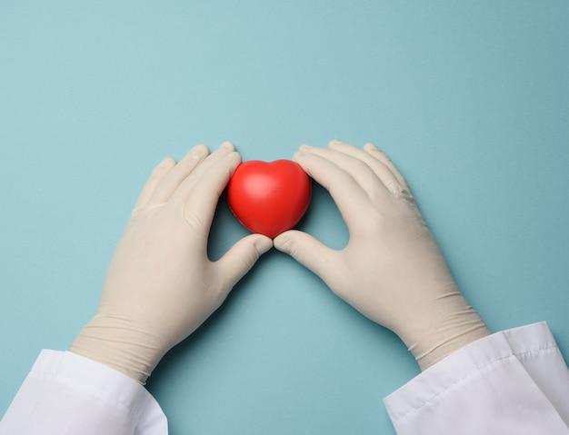 Twee dienen blauwe latexhandschoenen in houdend een rood hart, schenkingsconcept, sluit omhoog
