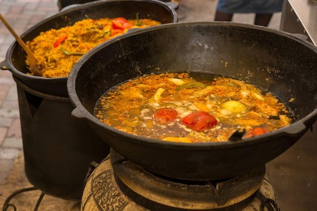 Twee diepe wokken met kleurrijke kruiden en groenten