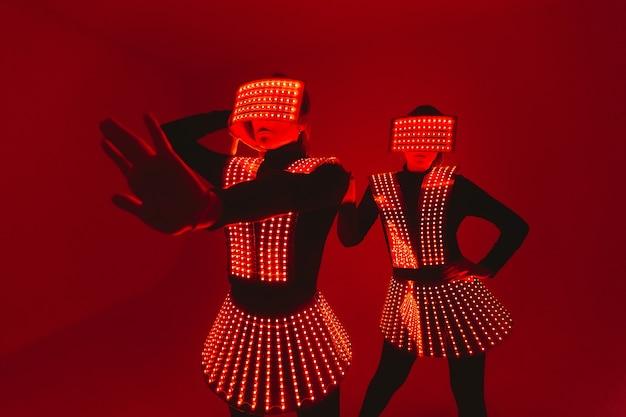 Twee discodansers bewegen zich in uv-kostuums.