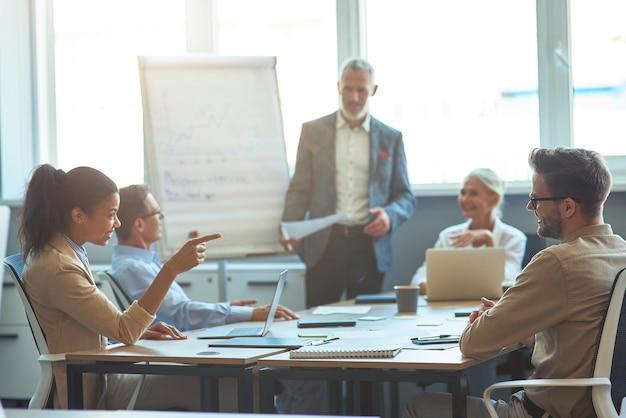 Twee diverse kantoormedewerkers praten en glimlachen terwijl ze een ontmoeting hebben met collega's in de moderne