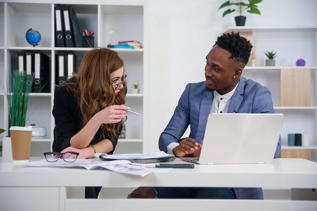 Twee diverse ondernemers chatten achter laptop op kantoor.