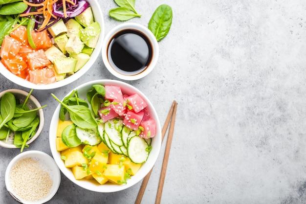 Twee diverse poke bowls met rauwe vis en groenten, ruimte voor tekst. bovenaanzicht, close-up. hawaiiaanse schotel, rustieke stenen achtergrond. gezond schoon eten concept. poke met plakjes rauwe vis, kopieer ruimte