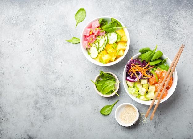 Twee diverse poke bowls met rauwe vis en groenten, ruimte voor tekst. bovenaanzicht. traditionele hawaiiaanse schotel, rustieke stenen achtergrond. gezond schoon eten concept. poke met plakjes rauwe vis, kopieer ruimte