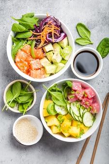 Twee diverse poke bowls, rauwe tonijn, zalm, groenten, fruit. bovenaanzicht, close-up. hawaiiaanse schotel, rustieke stenen achtergrond. gezond en schoon eten concept. poke met plakjes rauwe vis, eetstokjes