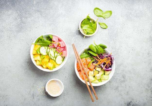 Twee diverse poke bowls, rauwe tonijn, zalm, groenten, fruit. bovenaanzicht. traditionele hawaiiaanse schotel, rustieke stenen achtergrond. gezond en schoon eten concept. poke met plakjes rauwe vis, eetstokjes
