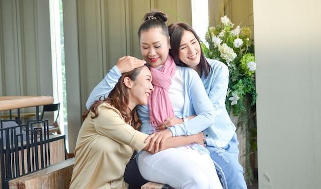 Twee dochters die geurige moeder met liefde omhelzen