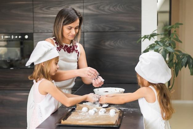 Twee dochters en moeder die koekje op keuken worktop voorbereiden