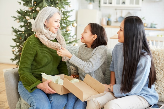 Twee dochters geven warme handgemaakte sjaal voor zijn moeder op eerste kerstdag die ze op de bank in de kamer zitten