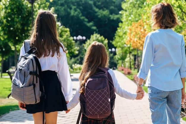 Twee dochters in schooluniform lopen samen met moeder naar school