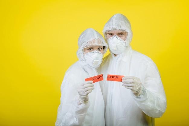 Twee dokters, een man en een vrouw in beschermende handschoenen en maskers, delen een rood teken van corovirus