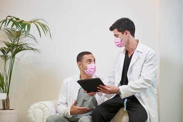 Twee doktoren in de wachtkamer met een masker die de resultaten becommentarieert met een tablet in de hand. gynaecologische, tandheelkundige of esthetische kliniek. medisch concept.