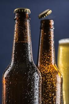 Twee donkere beslagen bierflesjes en een glas bier en schuim op de achtergrond op een groene en blauwe achtergrond.