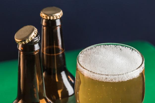 Twee donkere beslagen bierflesjes en een glas bier en schuim op een groene en blauwe achtergrond.