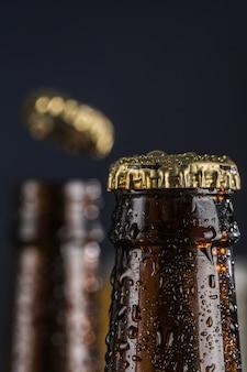 Twee donkere beslagen bierflesjes op een groene en blauwe achtergrond. vliegende dekking.