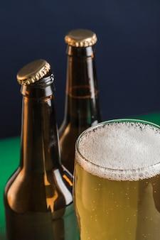 Twee donkere bierflesjes, een glas bier en schuim op een groene en blauwe achtergrond.